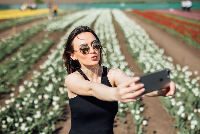 Junge Schönheitsabnutzungssonnenbrille macht selfie auf dem Tulpenblumengebiet am sonnigen Frühlingstag stockbilder