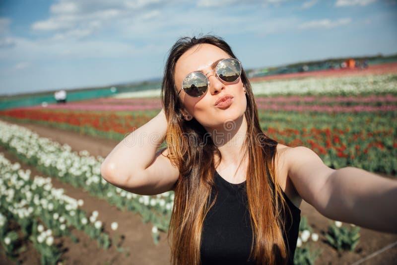 Junge Schönheitsabnutzungssonnenbrille macht selfie auf dem Tulpenblumengebiet am sonnigen Frühlingstag stockfotografie
