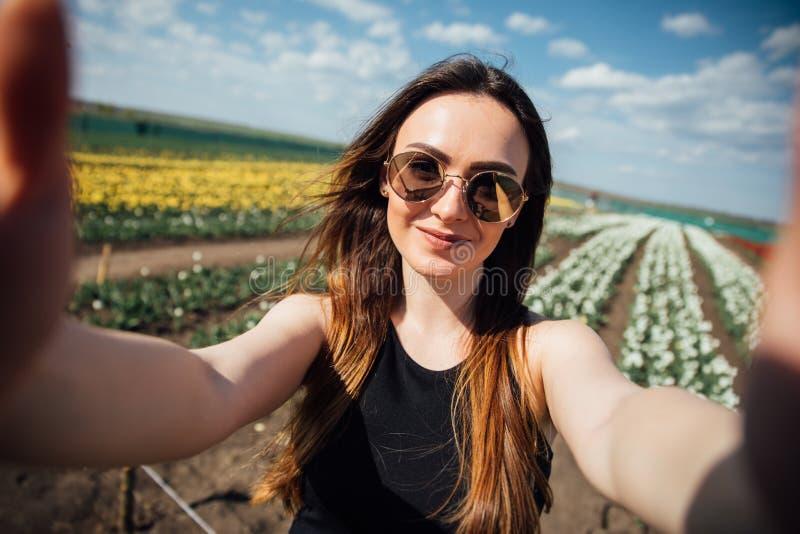 Junge Schönheitsabnutzungssonnenbrille macht selfie auf dem Tulpenblumengebiet am sonnigen Frühlingstag stockfoto