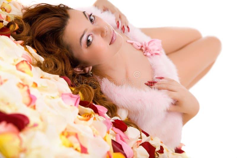 Junge Schönheitsfrau, die auf Blumenblatt liegt lizenzfreie stockfotos