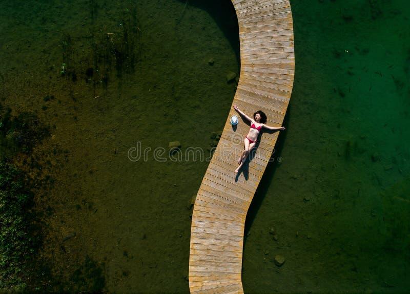 Junge Sch?nheitsfrau, die auf dem Seepier ein Sonnenbad nimmt stockbilder