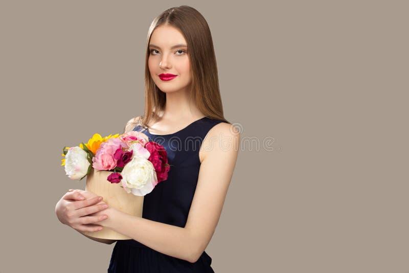 Junge Schönheitsfrau, die Blumen in ihren Händen hält lizenzfreies stockfoto