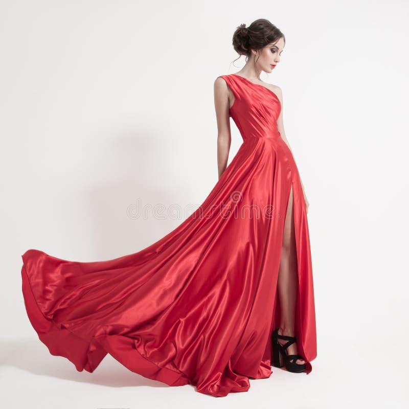 Junge Schönheitsfrau in flatterndem rotem Kleid. Weißer Hintergrund. stockfoto