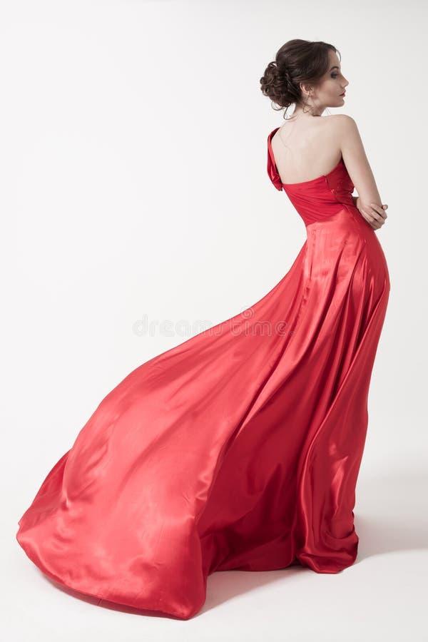 Junge Schönheitsfrau in flatterndem rotem Kleid. Weißer Hintergrund. stockbilder