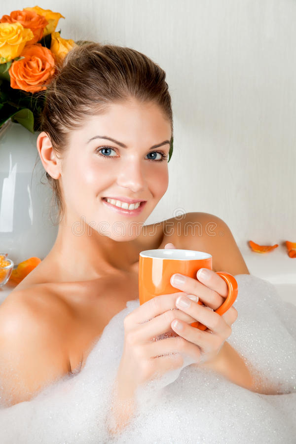 Junge Schönheitsfrau im Bad Kräutertee trinkend