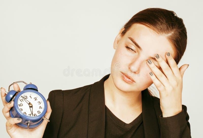 Junge Schönheitsfrau im Geschäftsartkostüm, das für frühen Morgen der Arbeit auf weißem Hintergrund mit dem Uhrtrinken aufwacht lizenzfreies stockfoto