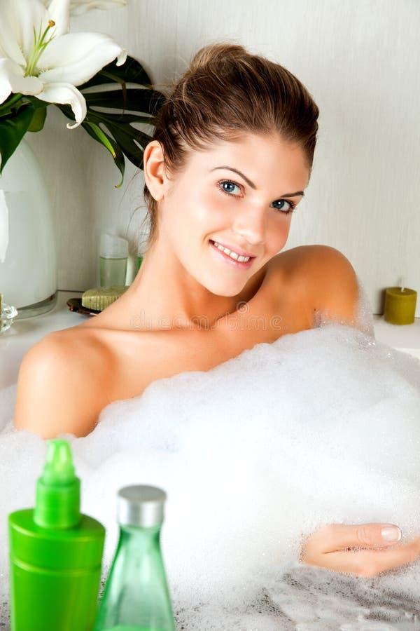 Junge Schönheitsfrau im vollen der Schaumgummibadewanne stockfoto
