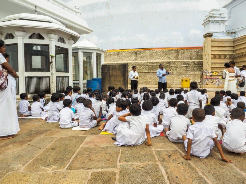 Junge Schüler Sri Lankan, die auf das briefinf über das größte stupa in Anuradhapura, Sri Langa hören lizenzfreie stockfotografie