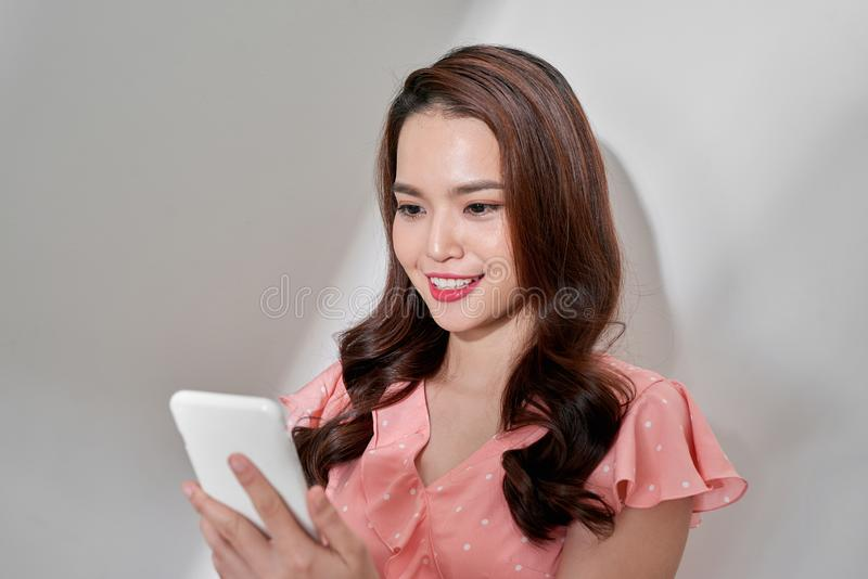Junge sch?ne ?berzeugte asiatische Frau, die Smartphone verwendet lizenzfreies stockfoto