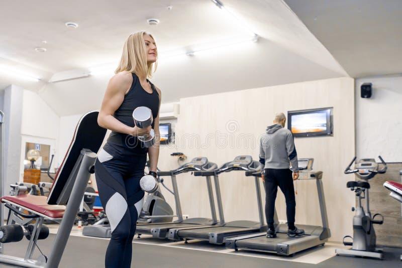 Junge sch?ne blonde Frau, die St?rke?bungen mit Dummk?pfen in der Turnhalle tut Sport, Eignung, Bodybuilding, Training, Training lizenzfreie stockfotos