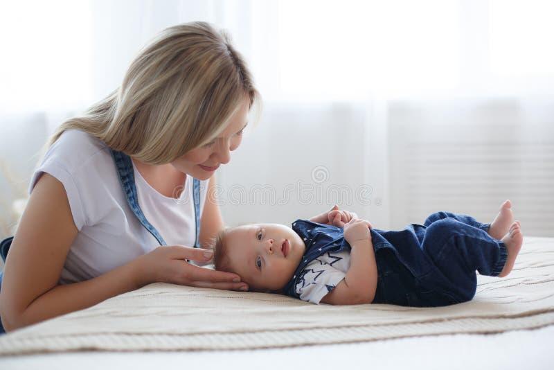 Junge sch?ne Mutter spielt in einem hellen Schlafzimmer mit einem jungen Sohn von 5 Monaten stockfotografie