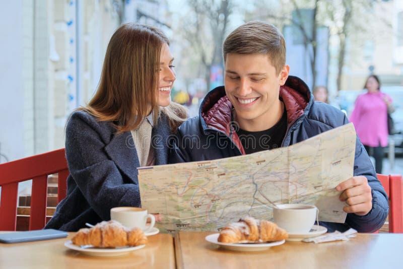 Junge sch?ne Paare von den Touristen, die Caf? im im Freien, Stadtplan lesend, trinkender Kaffee mit H?rnchen stillstehen lizenzfreies stockbild