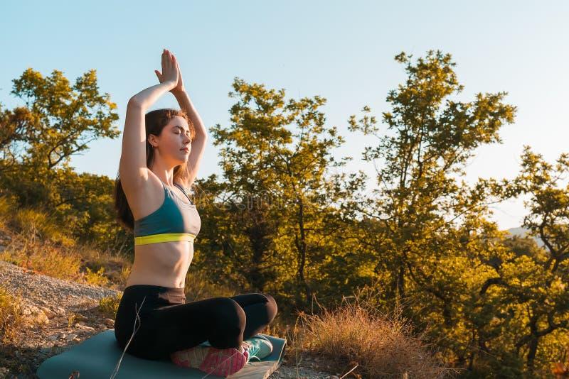 Junge Sch?nheit, die im Park meditiert Das Konzept von Yoga, von Sport und von Meditation lizenzfreies stockfoto