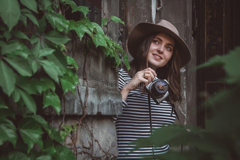 Junge Sch?nheit im Hut macht Foto mit altmodischer Kamera, drau?en stockbilder