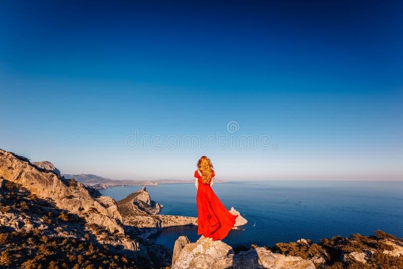 Junge Sch?nheit im roten Kleid, das zum Gebirgsmeer schaut lizenzfreies stockfoto