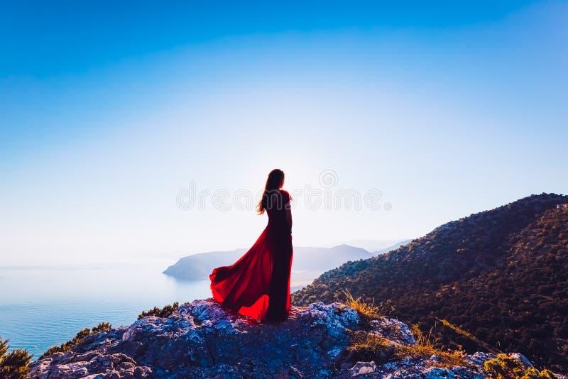 Junge Sch?nheit im roten Kleid, das zum Gebirgsmeer schaut stockfotografie