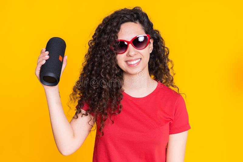 Junge Sch?nheit mit gelockter Frisur genie?end und am gelben Hintergrund tanzend Modernes modisches M?dchen, das auf h?rt lizenzfreies stockbild
