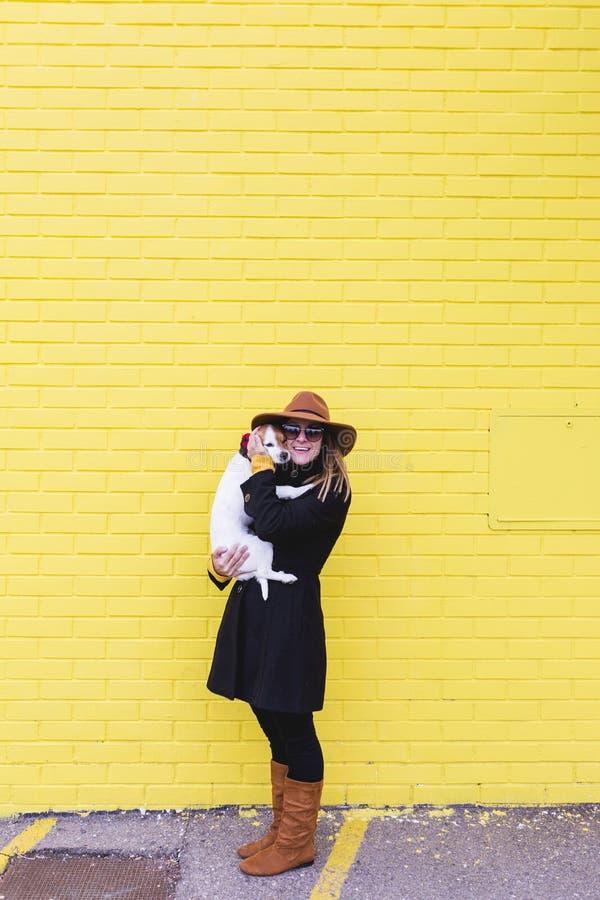 Junge Sch?nheitsholding und Lieben ihres Hundes F?rben Sie Backsteinmauer-Hintergrund gelb Liebe und Haustiere drau?en lizenzfreie stockfotografie