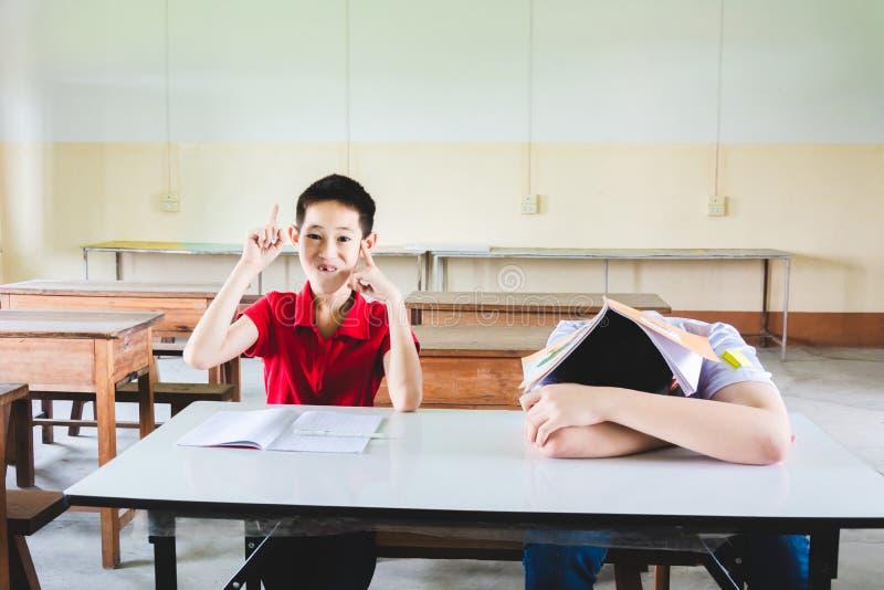 Junge schl?ft in der Klasse aber in anderer einer Hand bis zur Antwort die Frage stockbild