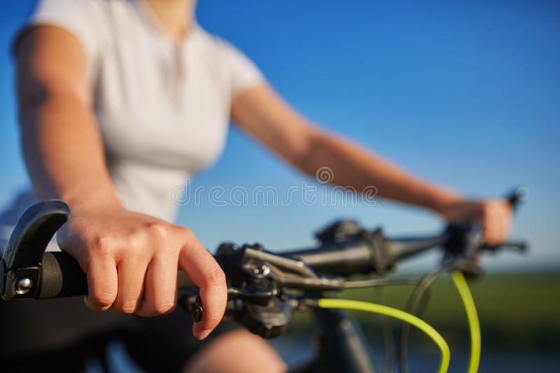 Junge schlanke Frau, die auf dem Fahrrad, Lenkstangen mit den Händen halten sitzt Frau in der Parksonnenuntergangbeleuchtung stockfotos