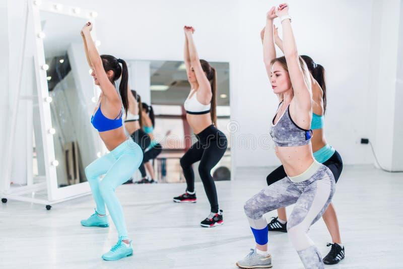 Junge schlanke Frauen, die untersetzte Übung der Unkosten während des Gruppentrainings in der Turnhalle tun stockfoto
