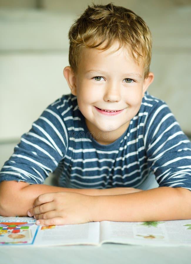 Junge schreibt auf sein Schreibheft stockbilder
