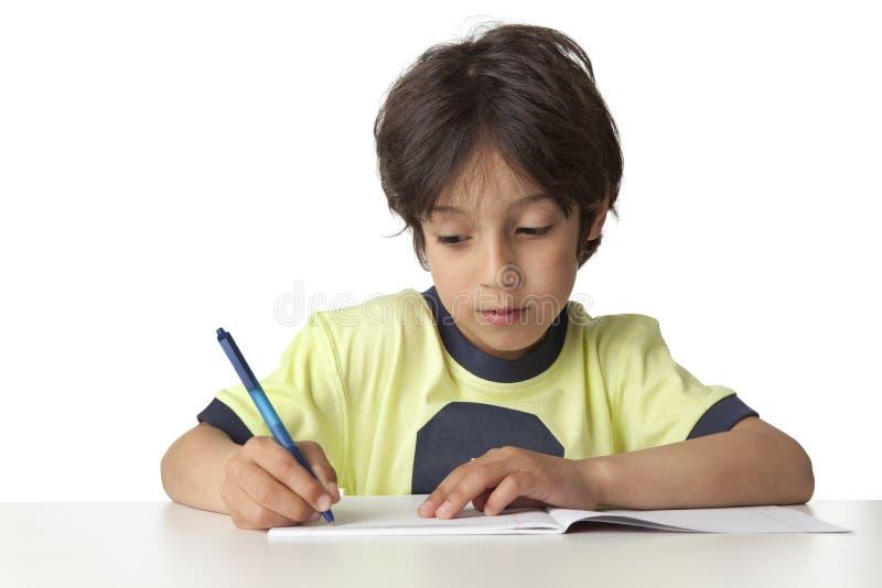 Junge schreibt in sein Notizbuch stockbild