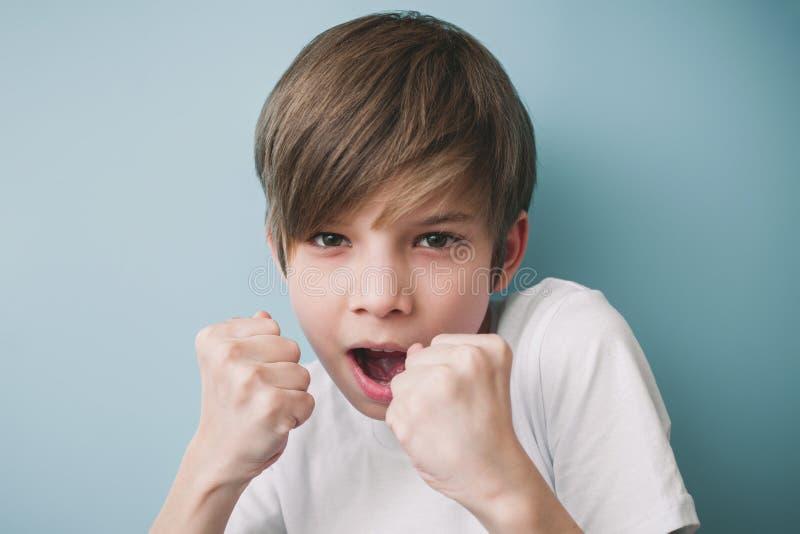 Junge schreit und droht im Scherz mit seinen Fäusten, wenn er St. kämpft stockfotografie