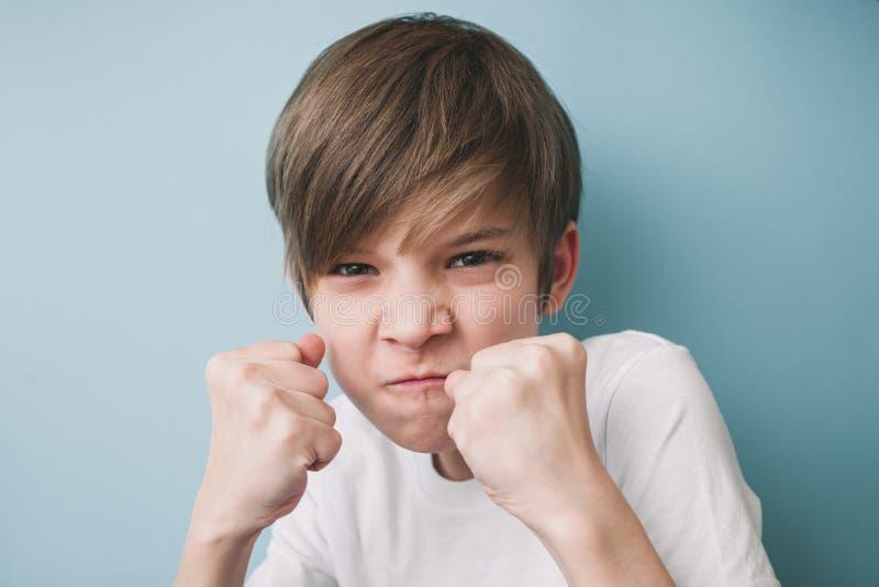 Junge schreit und droht im Scherz mit seinen Fäusten, wenn er St. kämpft lizenzfreie stockfotografie