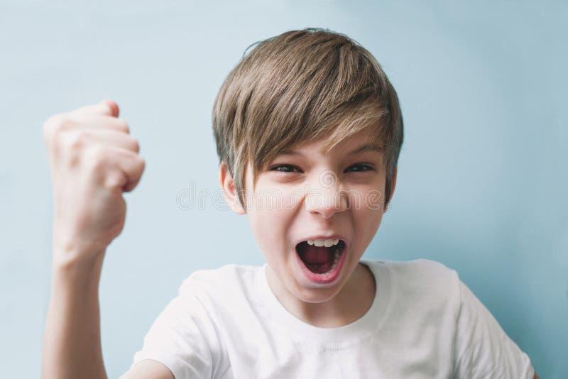 Junge schreit und droht im Scherz mit seiner Faust lizenzfreie stockfotos