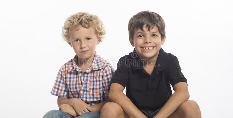 Junge, Schule alterten die Jungen, die zusammen sitzen lizenzfreie stockbilder