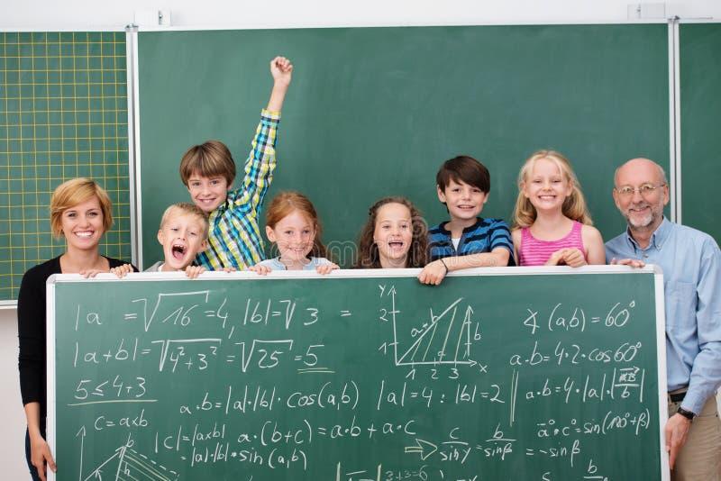 Junge Schulkinder, die mit einer Tafel aufwerfen stockbild
