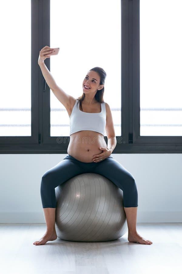 Junge schwangere Frau, die ein selfie mit Handy beim Entspannungsübung auf Eignungsball zu Hause tun nimmt stockfoto