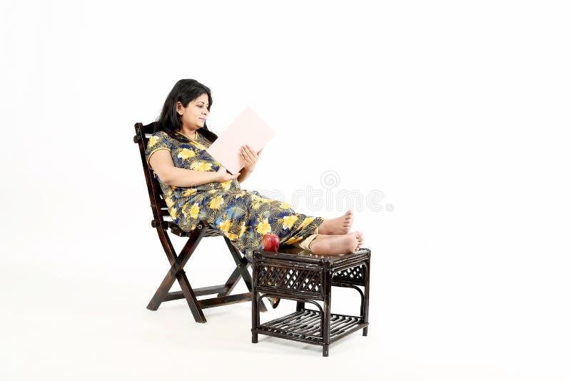 Junge schwangere Frau liest Babyzeitschrift stockfoto
