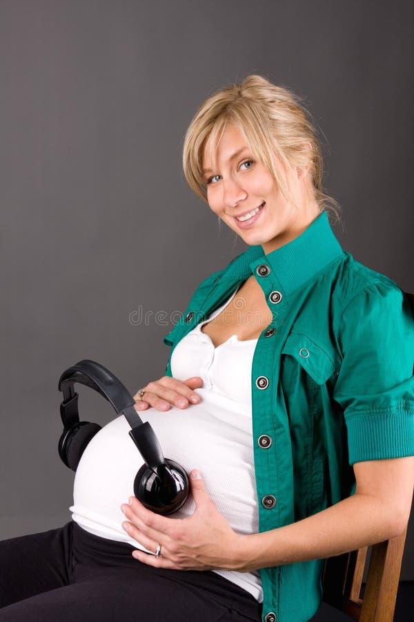 Junge-schwangere Frau - mit Musik-Kopfhörern lizenzfreies stockbild
