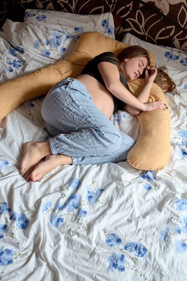 Junge-schwangere Frau Schwangere Sch?nheit schl?ft auf Mutterschaftskissen im Bett stockbild