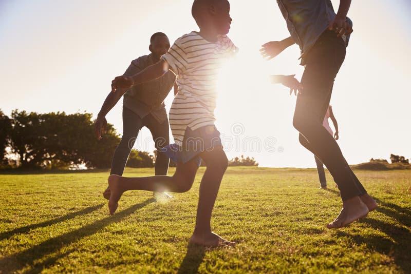 Junge schwarze Familie, die auf einem Gebiet im Sommer spielt stockbild