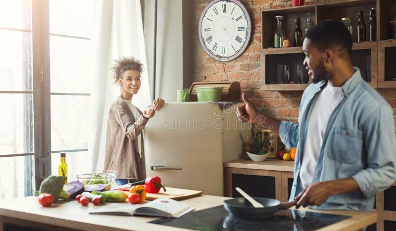 Junge schwarze Familie, die zusammen Abendessen in Küche vorbereitet stockfoto
