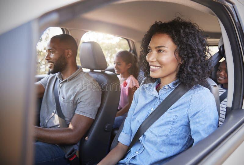 Junge schwarze Familie mit Kindern in einem Auto, das auf Autoreise geht stockfotografie