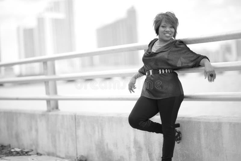 Junge schwarze Frau, die auf dem Geländer sich lehnt lizenzfreie stockbilder