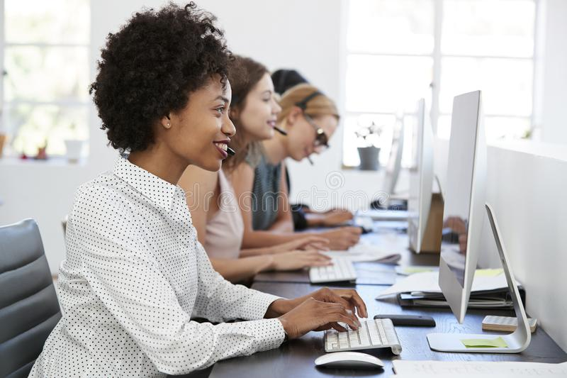 Junge schwarze Frau, die am Computer im Büro mit Kopfhörer arbeitet stockbild