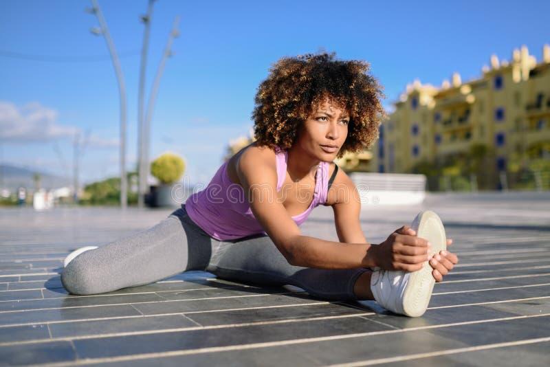 Junge schwarze Frau, die das Ausdehnen tut, nachdem draußen laufen lizenzfreie stockfotos