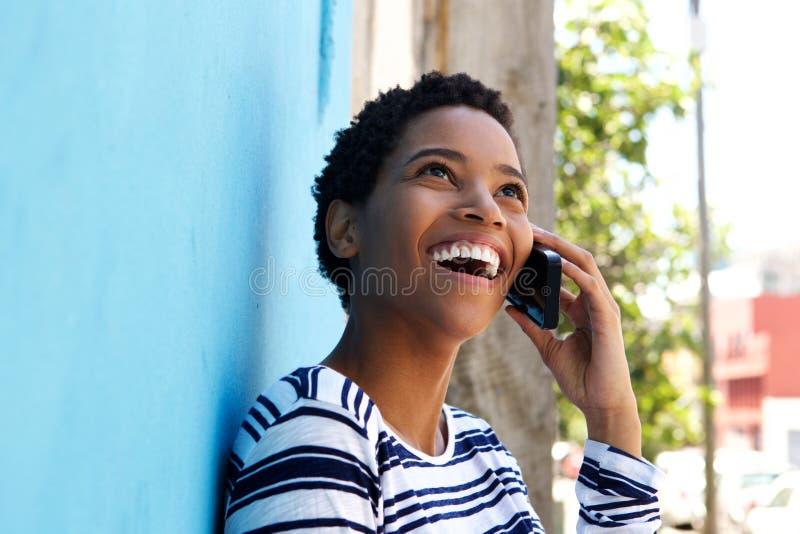 Junge schwarze Frau, die an der Wand sich lehnt und am Handy spricht stockfotografie