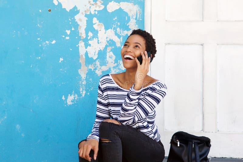 Junge schwarze Frau, die draußen mit Handy lächelt und sitzt lizenzfreie stockfotos