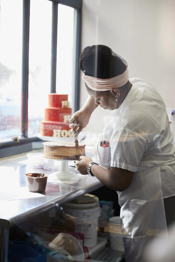 Junge schwarze Frau, die einen Kuchen an einer Bäckerei bereift lizenzfreies stockbild