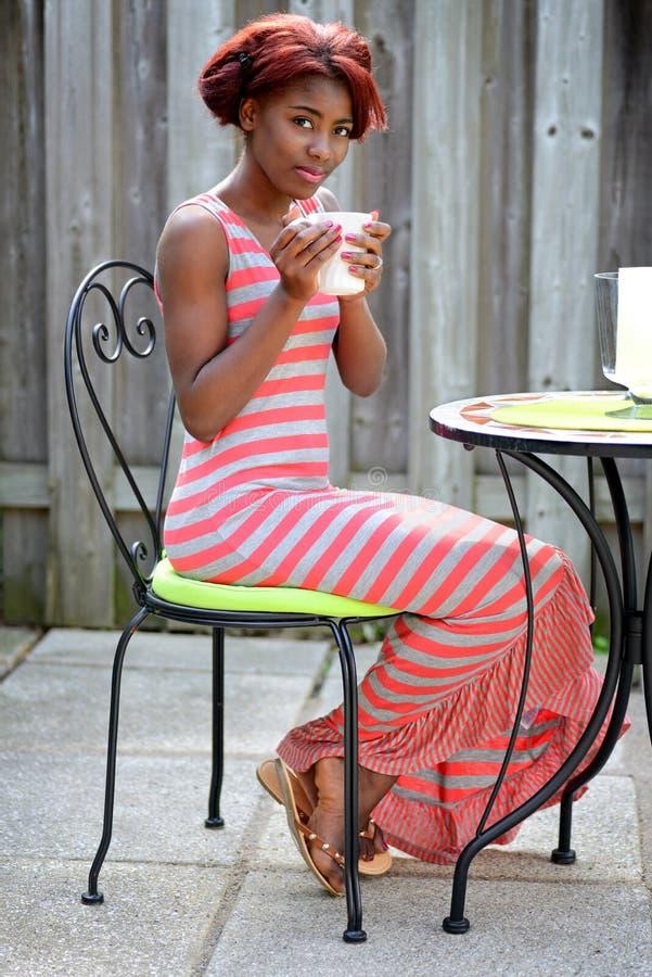 Junge schwarze Frau, die Kaffee auf dem Patio genießt lizenzfreie stockfotografie