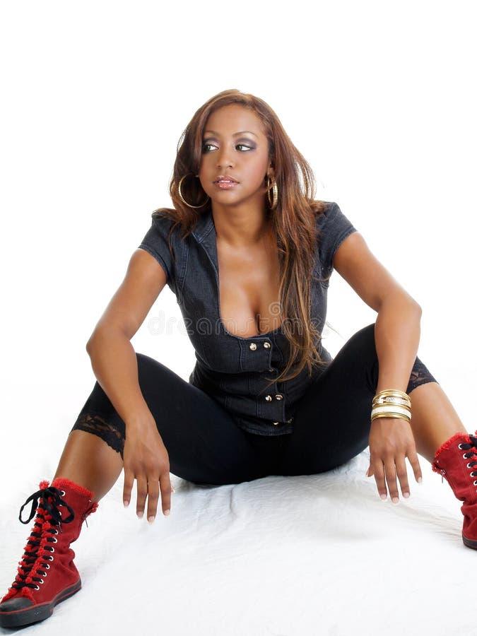 Junge schwarze Frau, die mit roten Schuhen sitzt stockbild