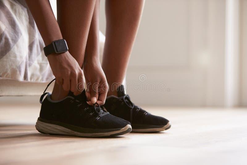 Junge schwarze Frau, die Sportschuhe, Nahaufnahme bindet lizenzfreie stockfotos