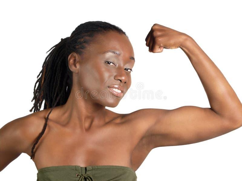 Junge schwarze Frau, die starkes gebogenes bicep zeigt lizenzfreie stockbilder