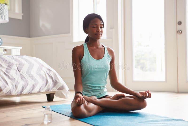 Junge schwarze Frau, die zu Hause Yoga im Lotussitz tut stockbild